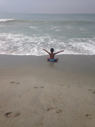My son praising on the beach.